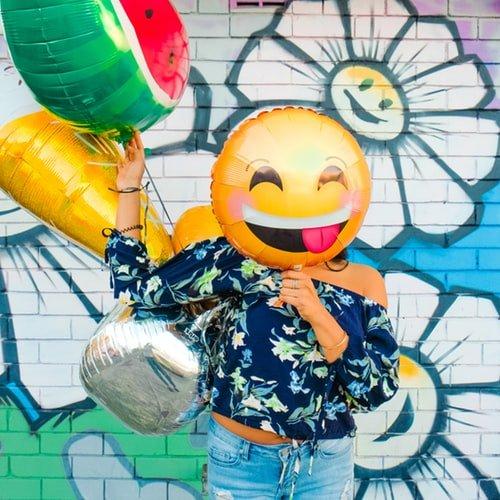 Mulher com balão de emoticon em frente ao rosto
