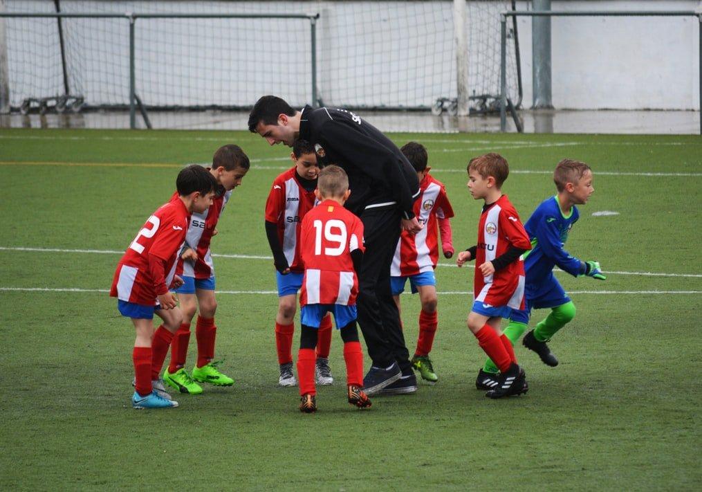 Treinador com calça e jaqueta preta no meio de pequenos meninos usando uniformes e chuteiras.