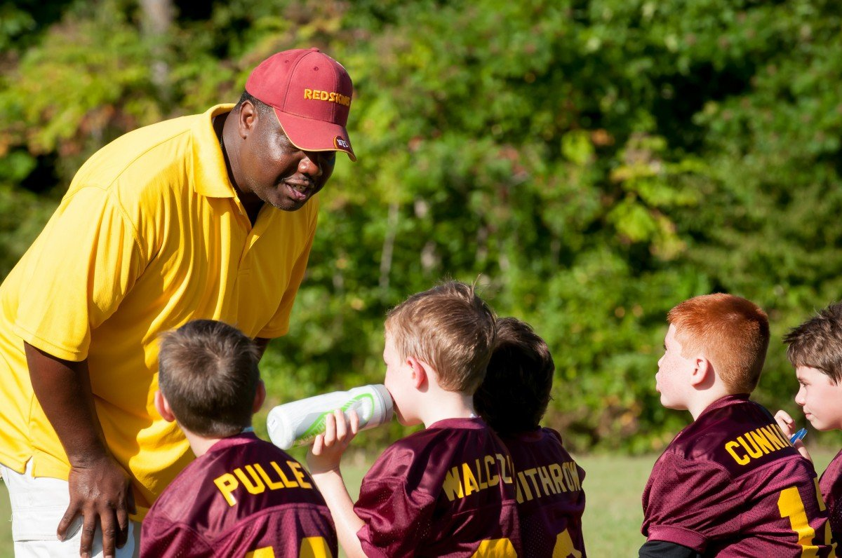 Treinador usando camiseta amarela e boné de seu time, falando com seus jogadores, pequenos meninos com uniforme vermelho do time.