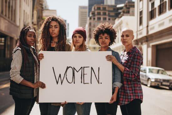 Mulheres segurando um cartaz escrito em inglês mulher.