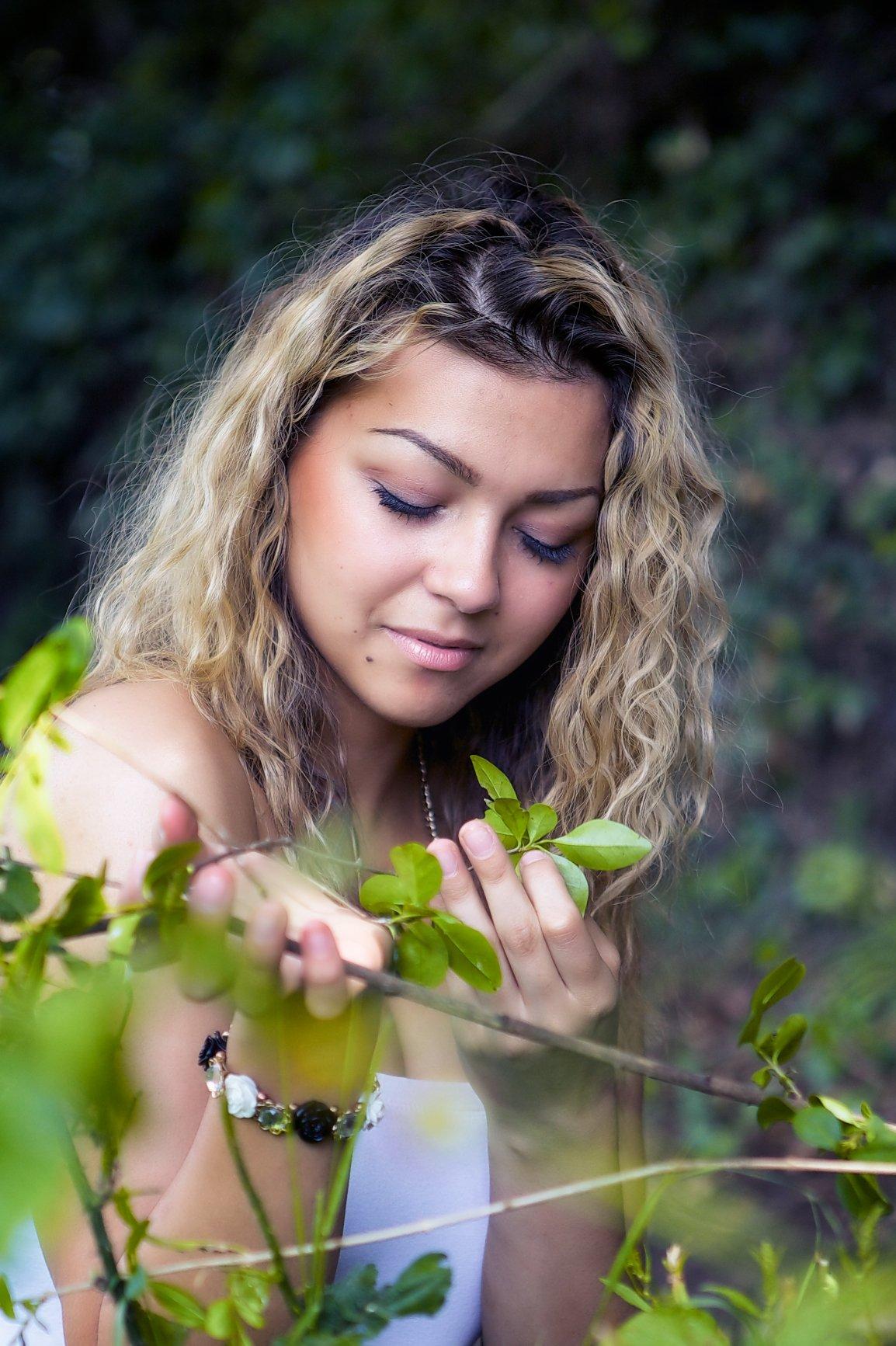 Mulher segurando planta com os olhos fechados