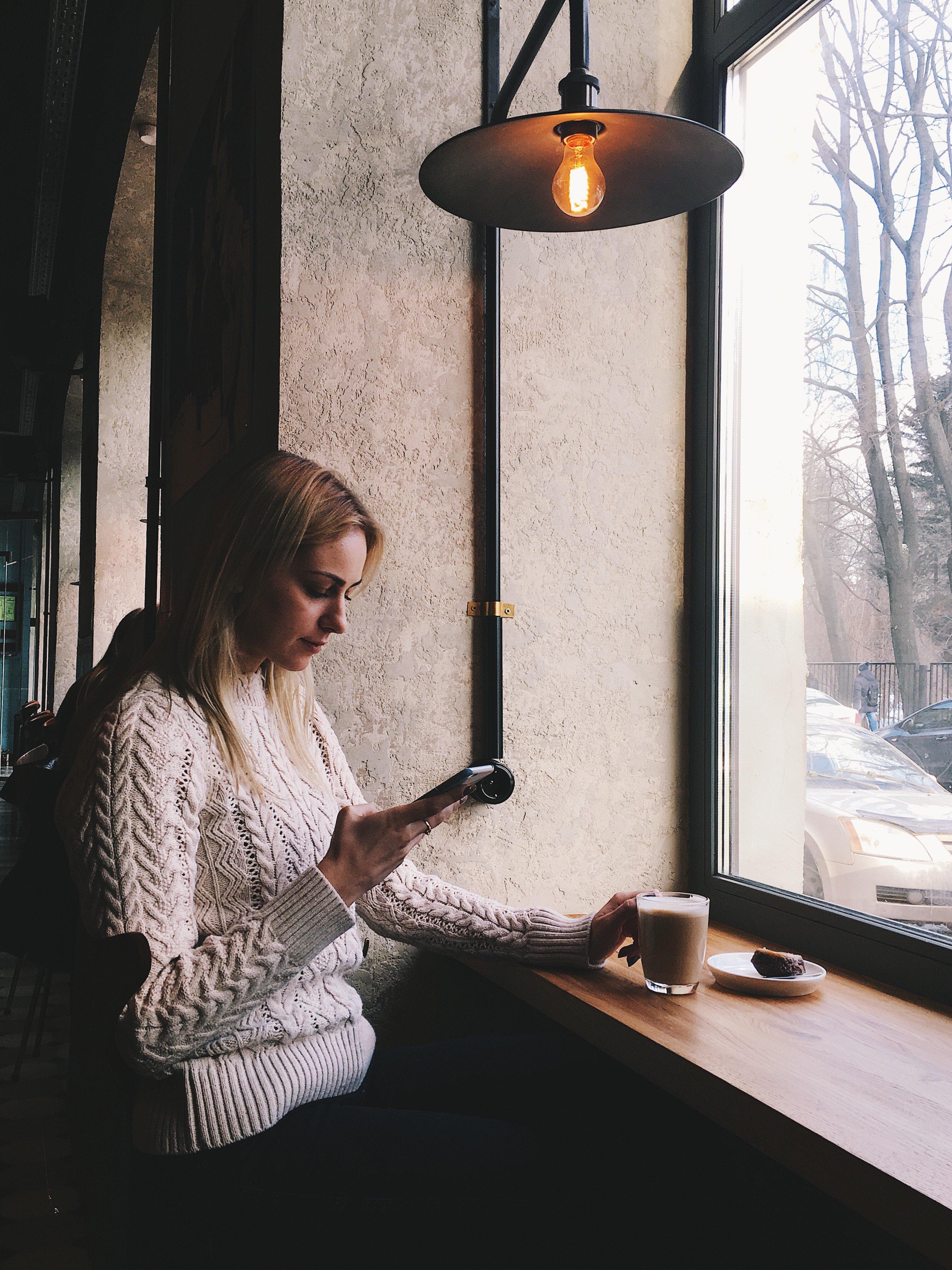 Mulher so celular em uma lanchonete