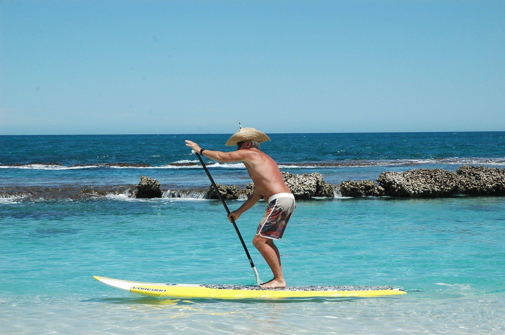 Idoso praticando em pé em prancha de surfe
