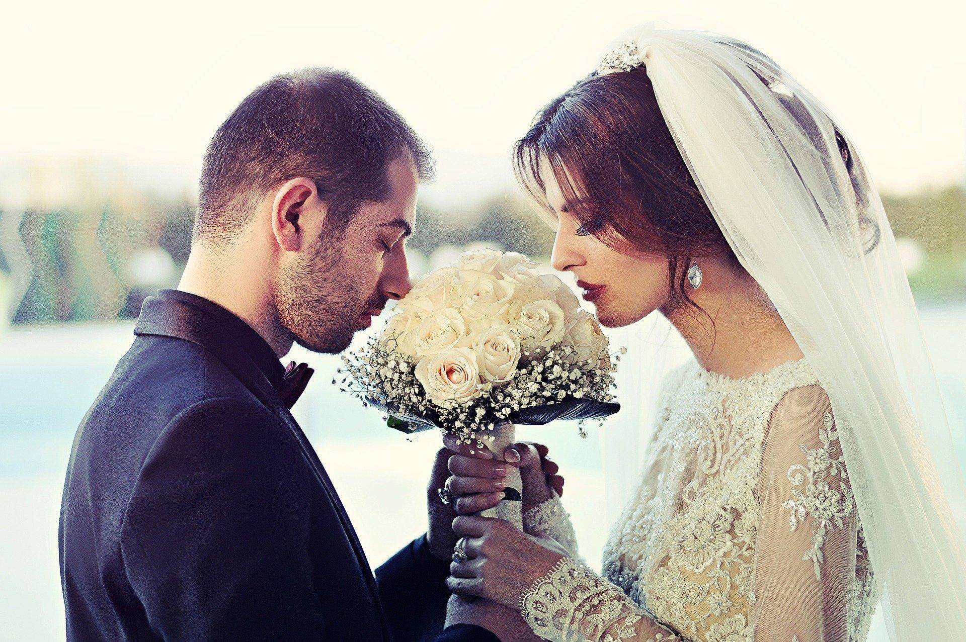 Foto de noivos de mãos dadas, ambos segurando um buquê