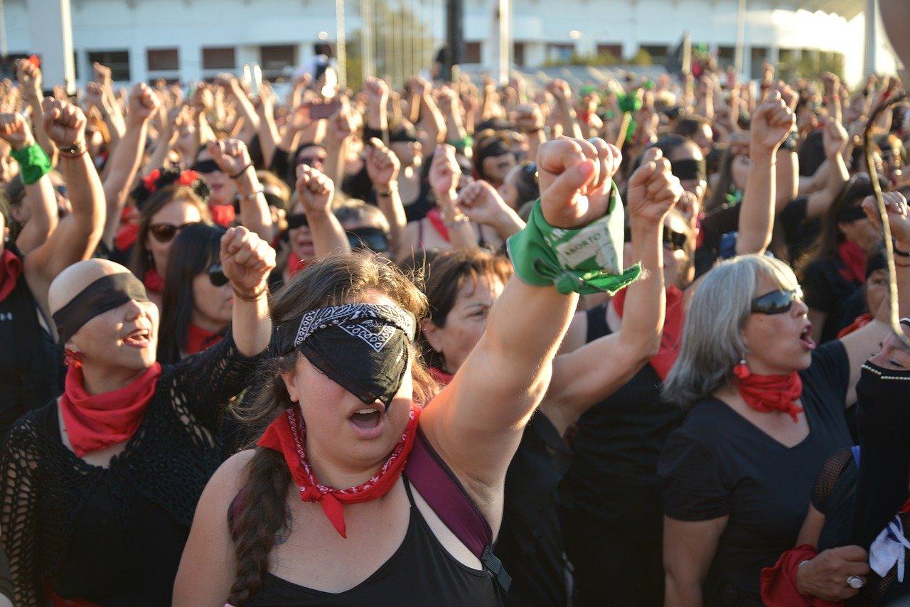 Muitas mulheres protestando com os punhos esquerdos para o alto e o os olhos cobertos, com bandanas ou óculos escuros.