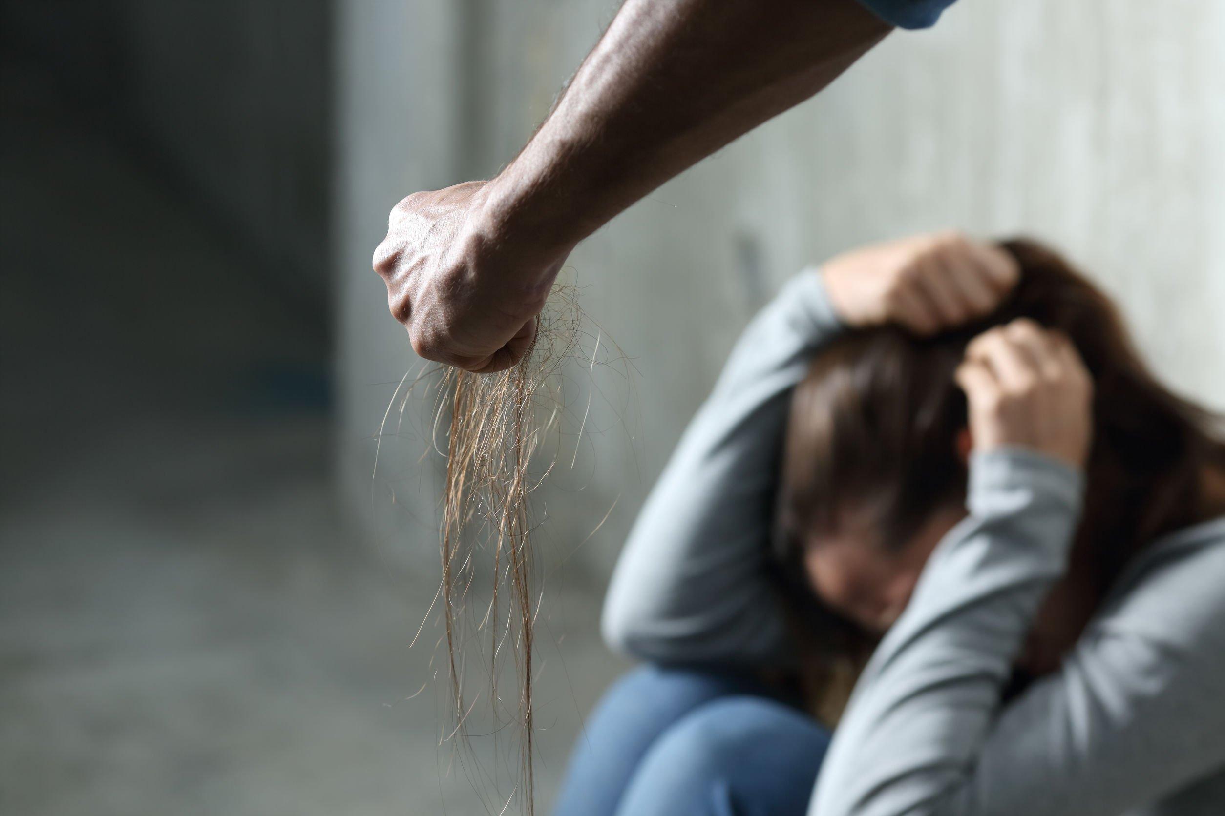 Mulher sentada no chão com a cabeça baixa encostada em seus joelhos flexionados e suas mãos tentando cobrir sua cabeça. Em foco, o braço de um homem segurando uma mecha de cabelo arrancado.
