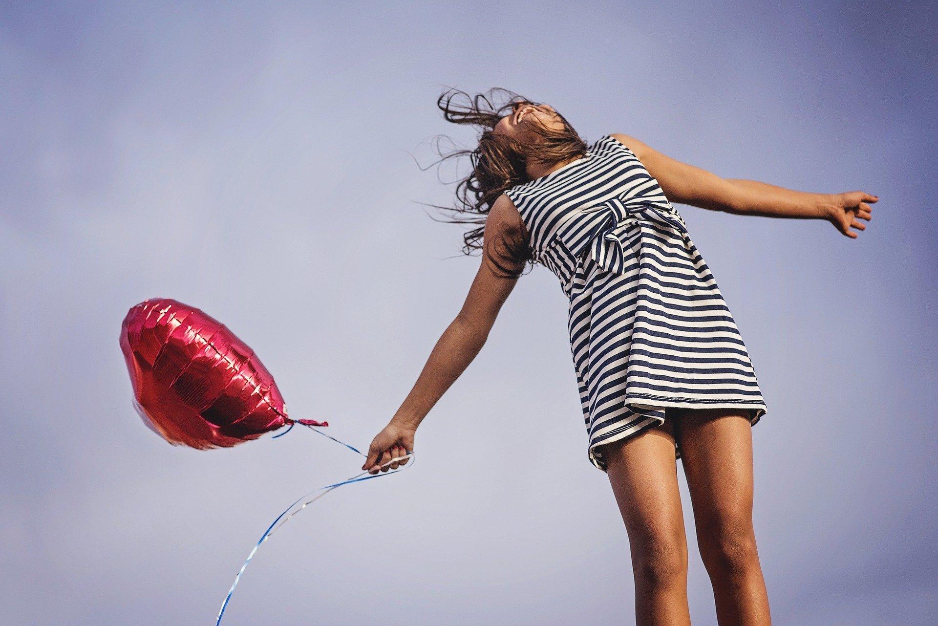 Menina segurando balão de coração
