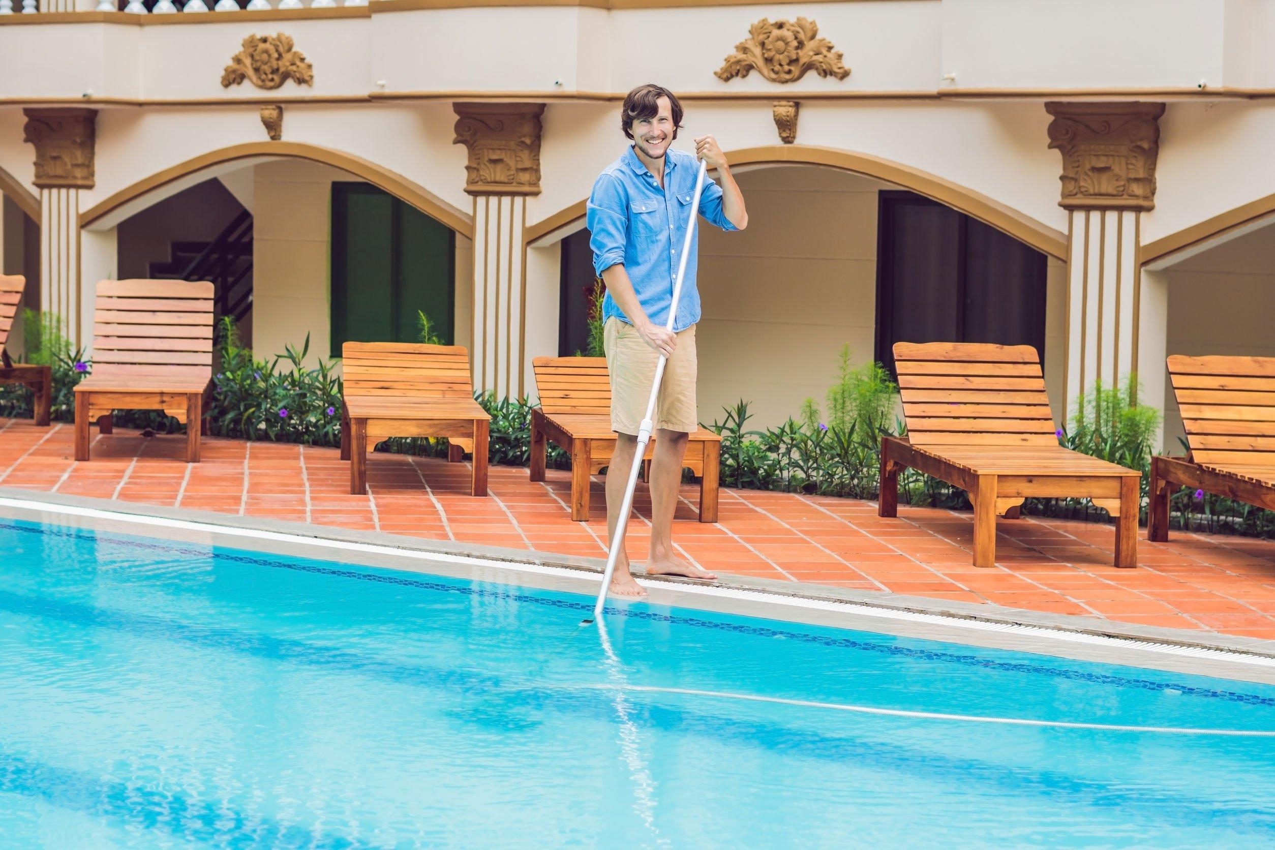 Homem limpando piscina