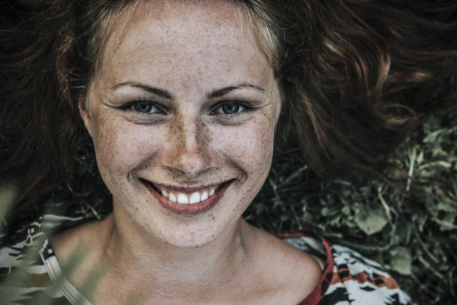Mulher com sardas sorrindo