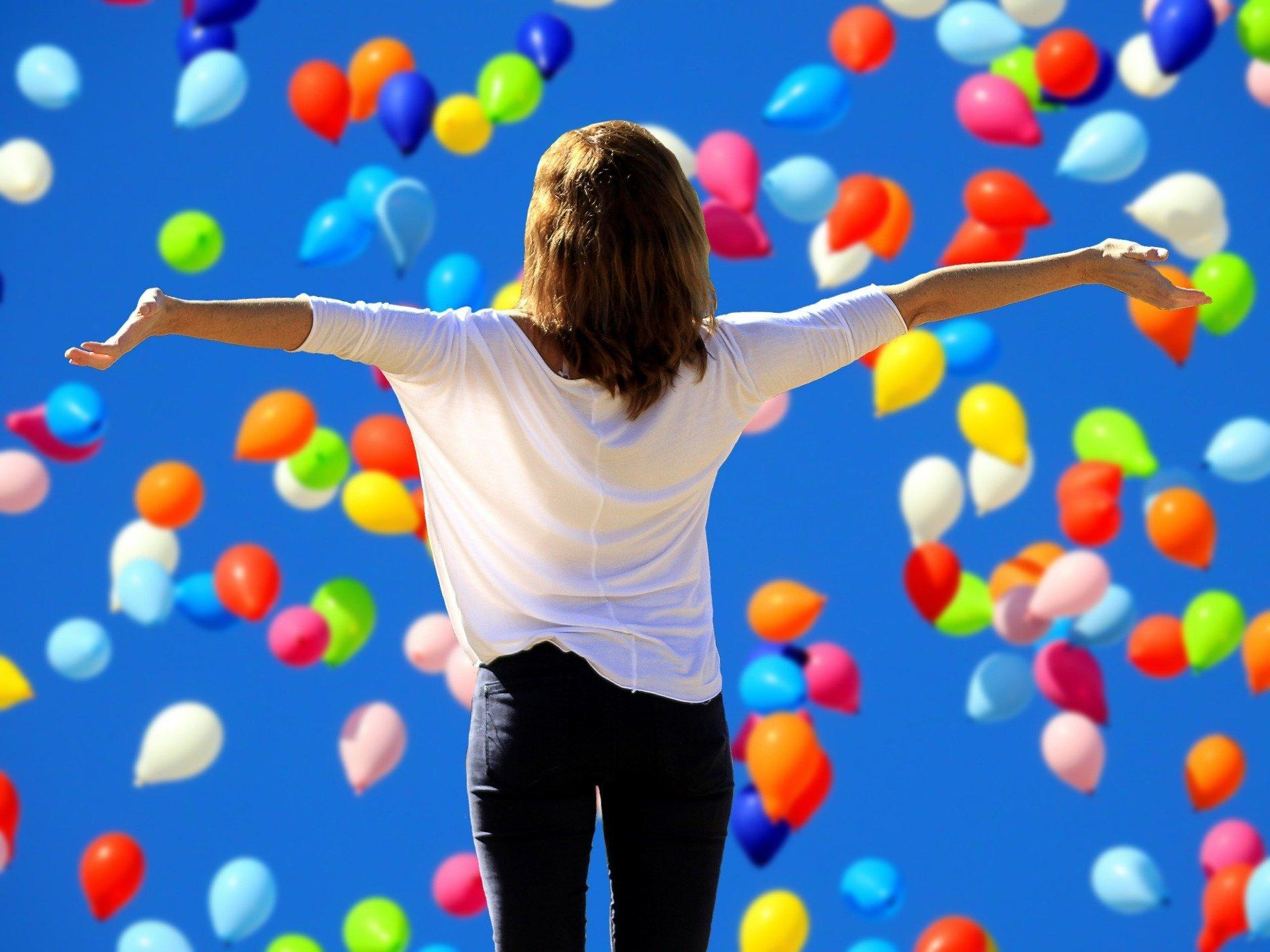 Mulher com braços abertos, ao fundo há diversos balões coloridos voando no céu