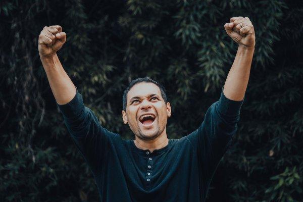Homem com braços pro alto, em sinal de comemoração, cercado de árvores