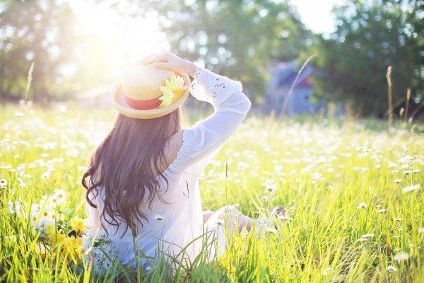 Mulher em campo de flores com a mão no chapéu