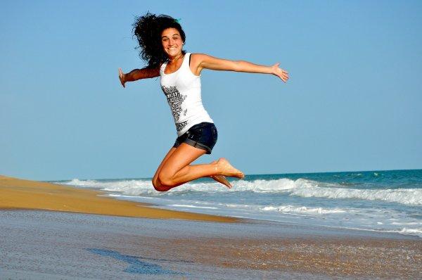 Mulher sorrindo pulando em praia