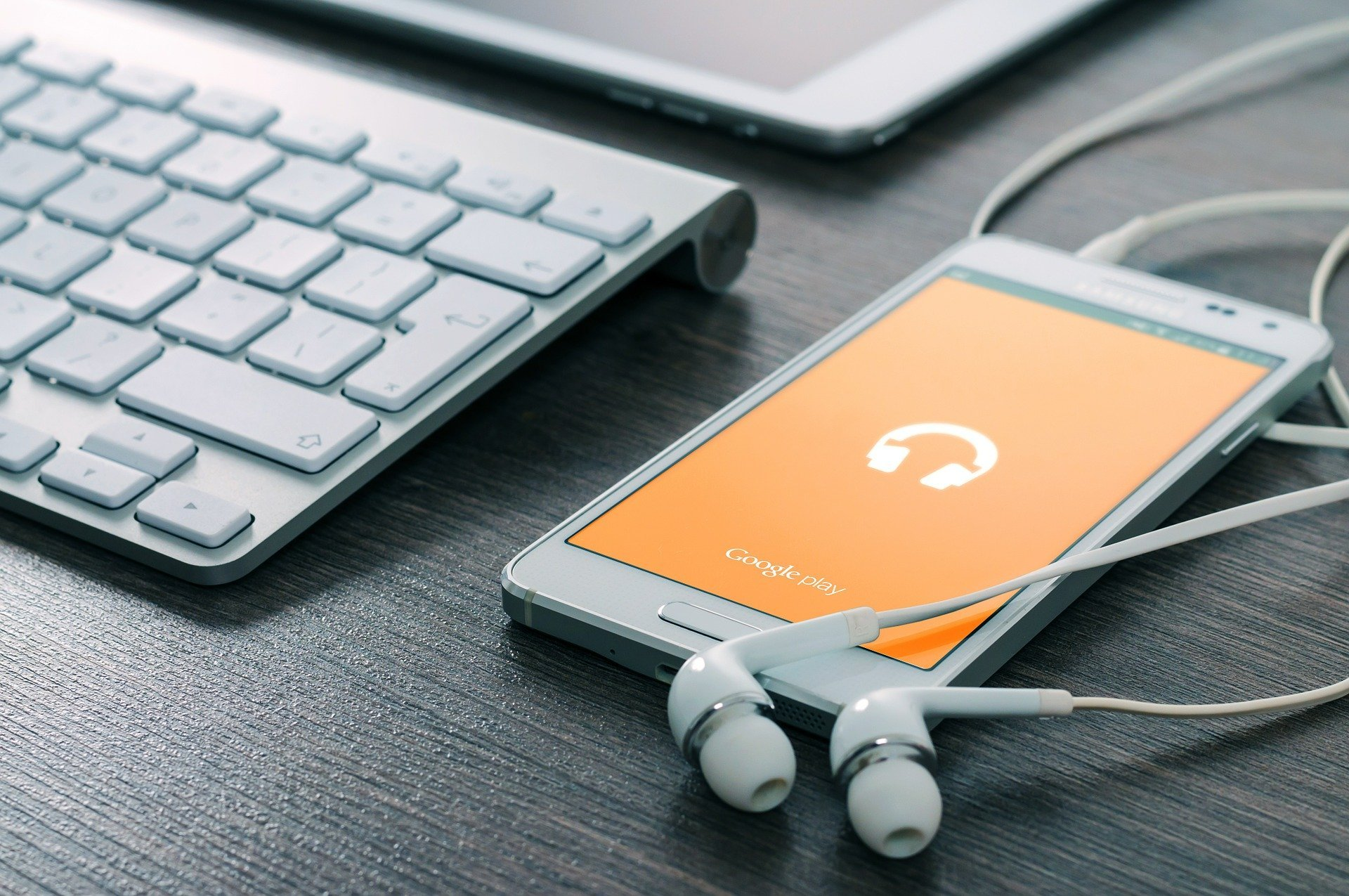 Celular e fones de ouvido em cima de mesa