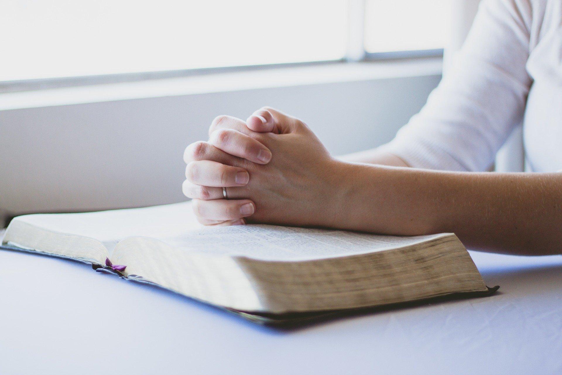 Mão de pessoa orando em cima de bíblia