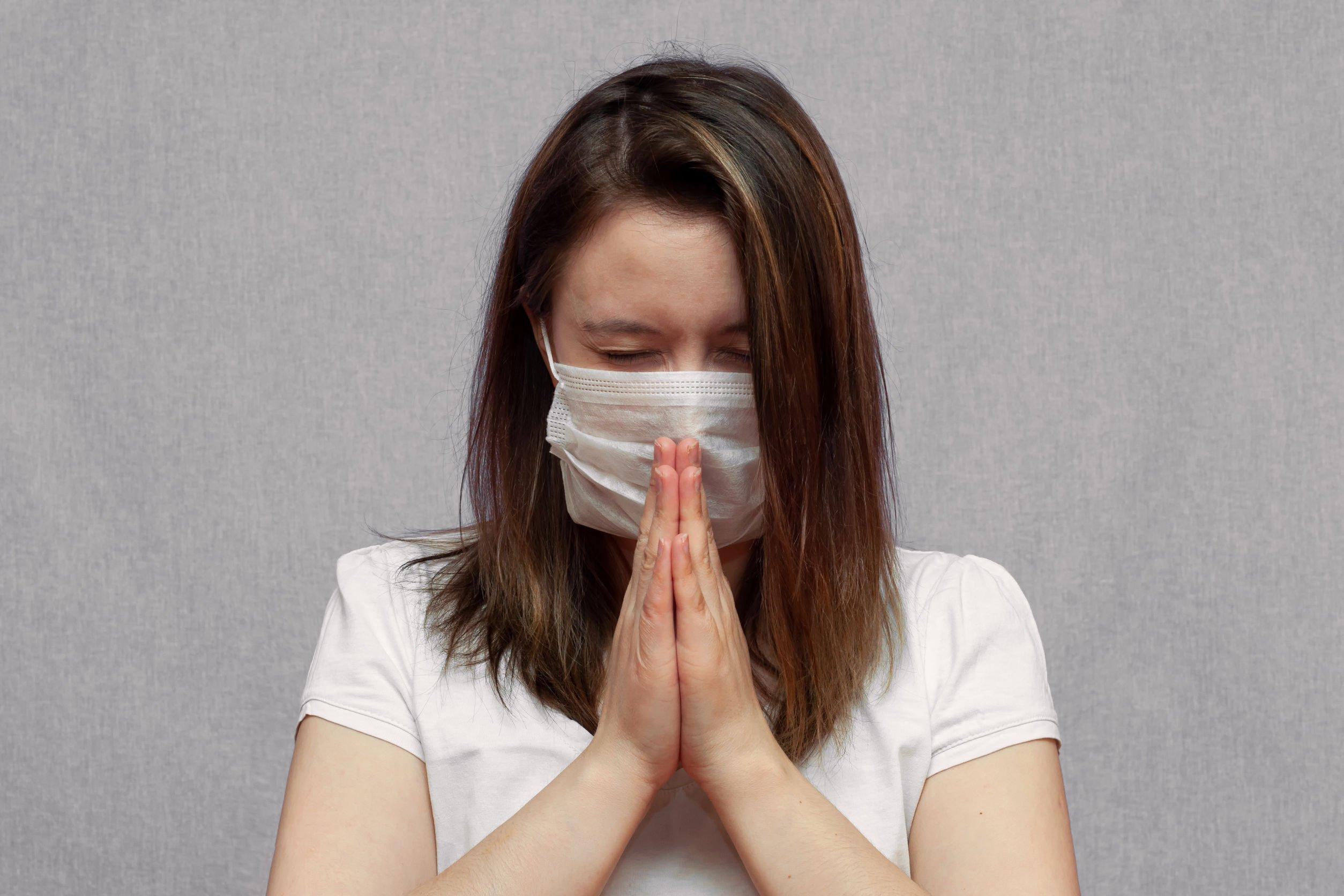 Mulher usando máscara branca, de olhos fechados e mãos unidas, orando