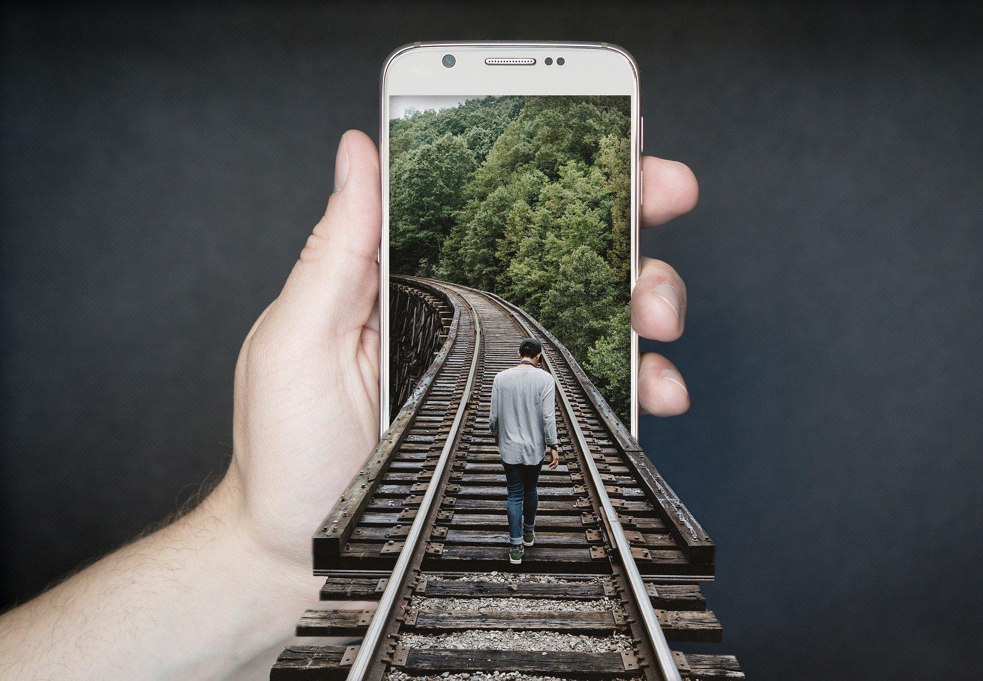 Pessoa segurando celular com desenho 3D de homem caminhando em trilho de trem saindo da tela do celular