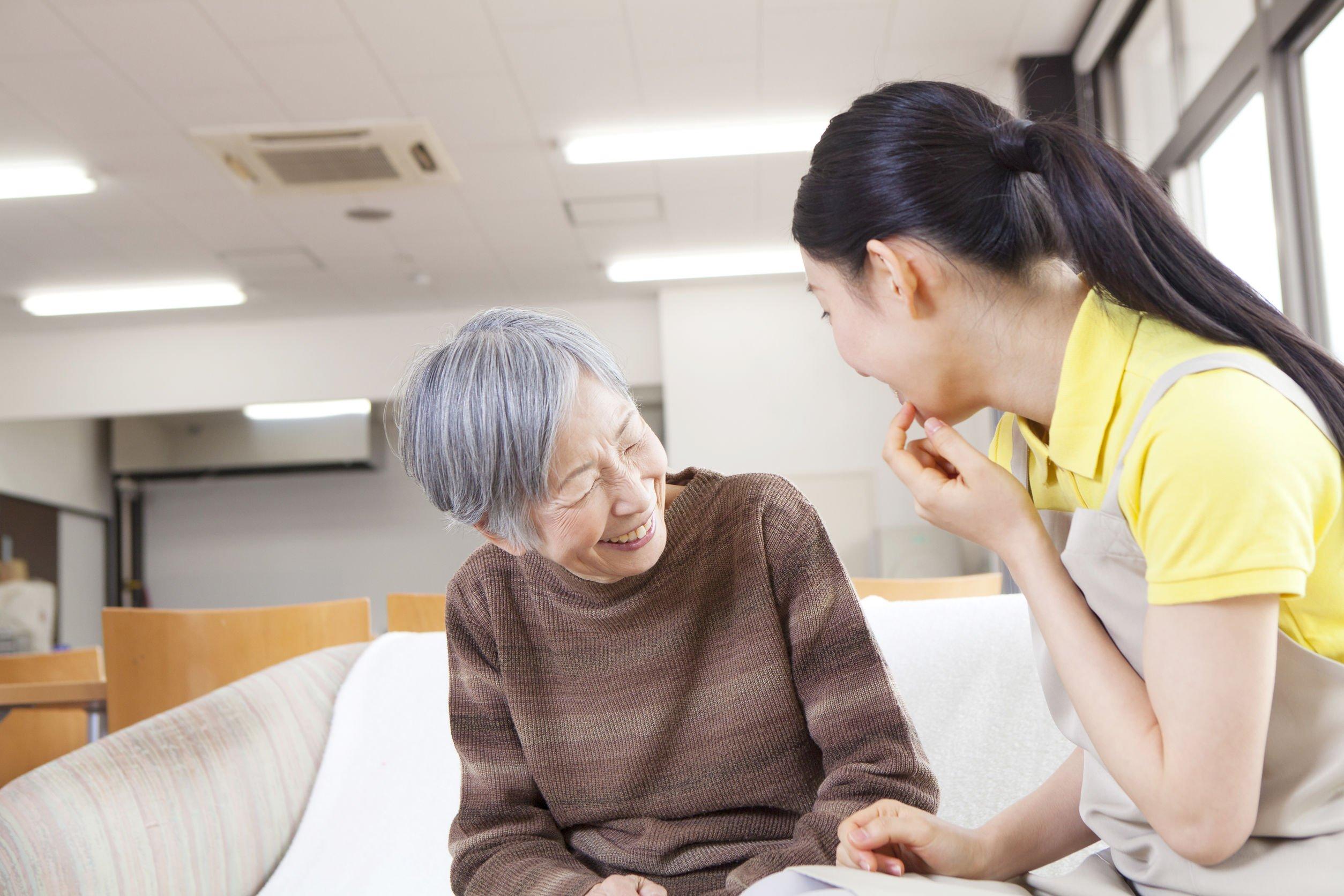 Senhora asiática, idosa, sentada em cama ao lado mulher cuidadora, sorrindo enquanto conversam