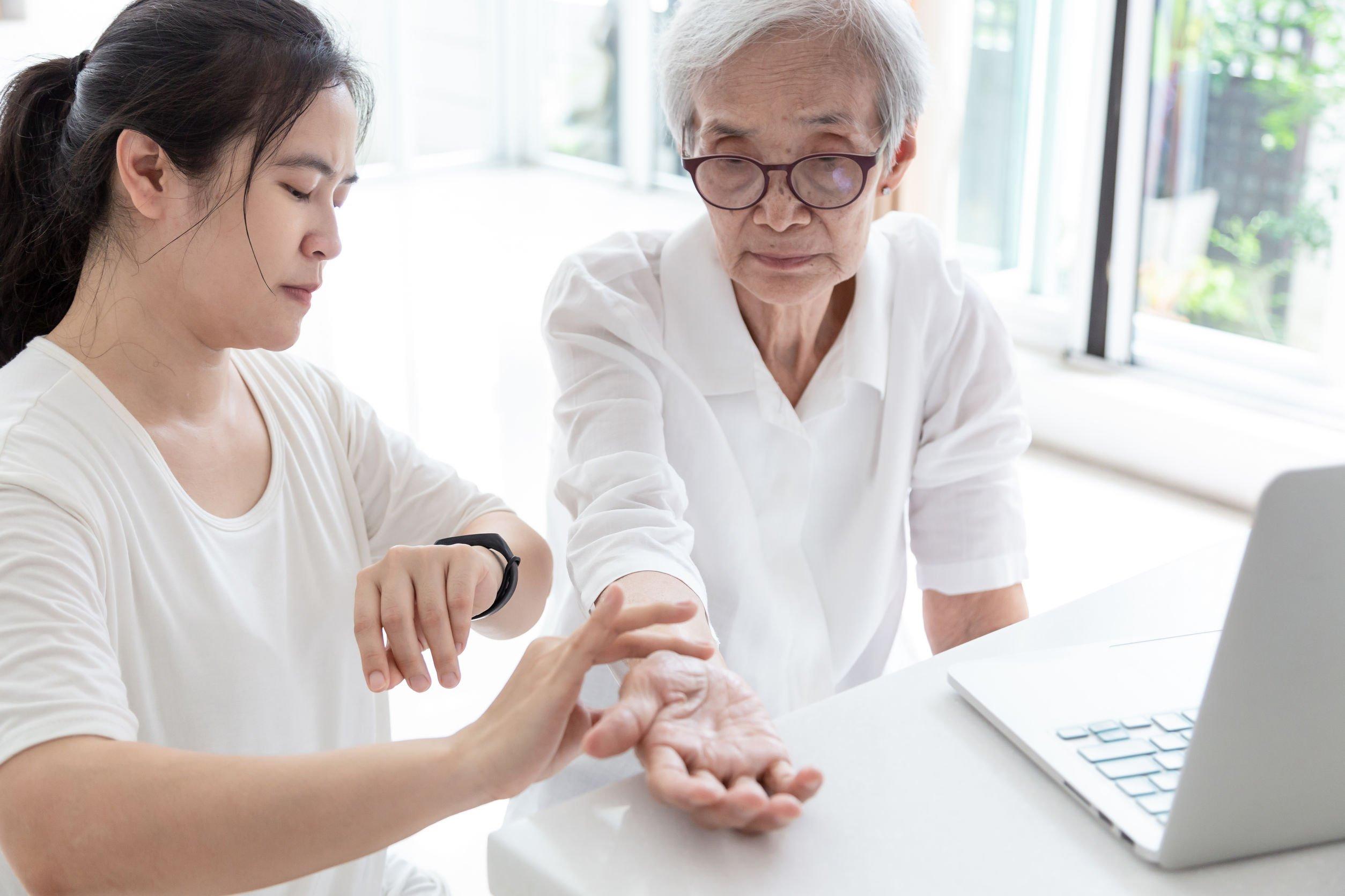 Mulher cuidadora segurando braço de senhora de idade para verificar a frequência cardíaca dela