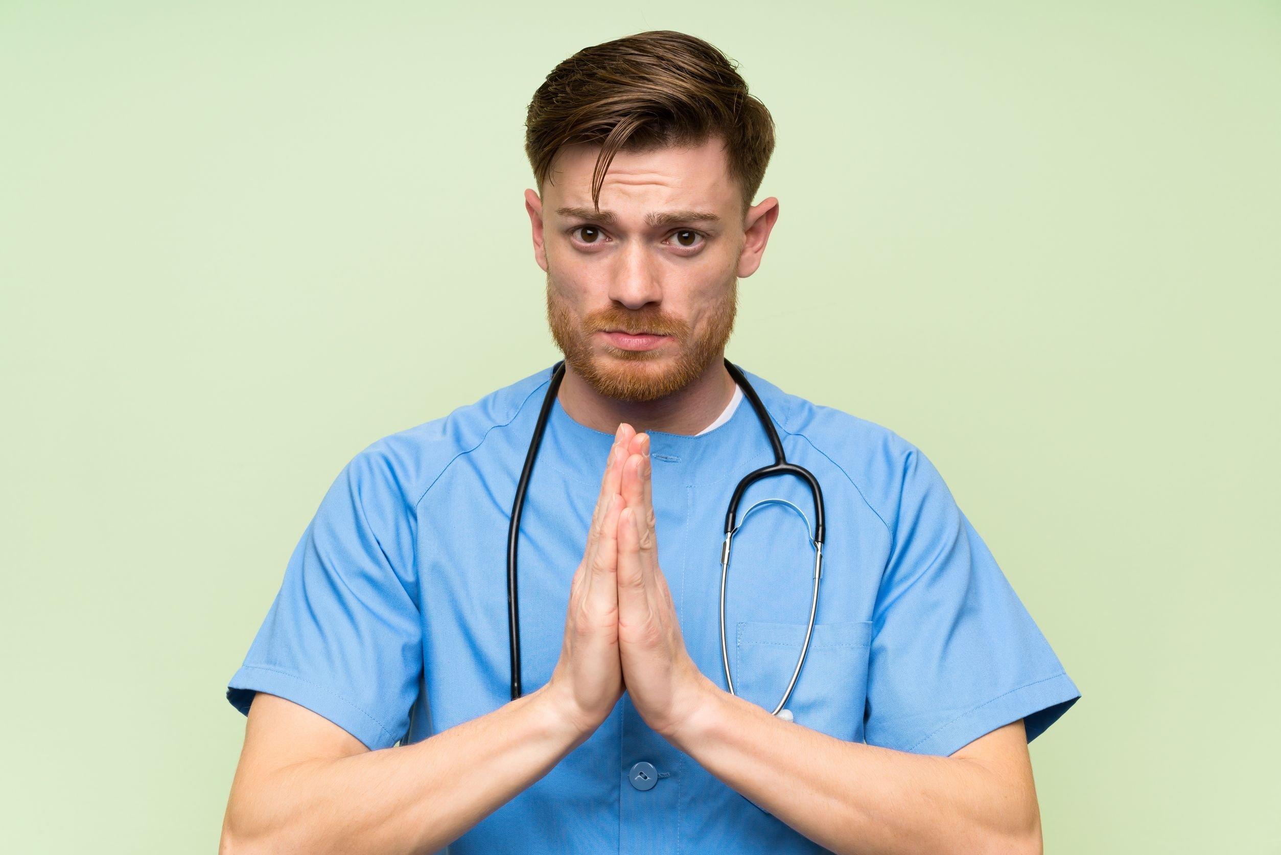 Enfermeiro com mãos juntas e expressão de preocupação, com estetoscópio em volta de pescoço