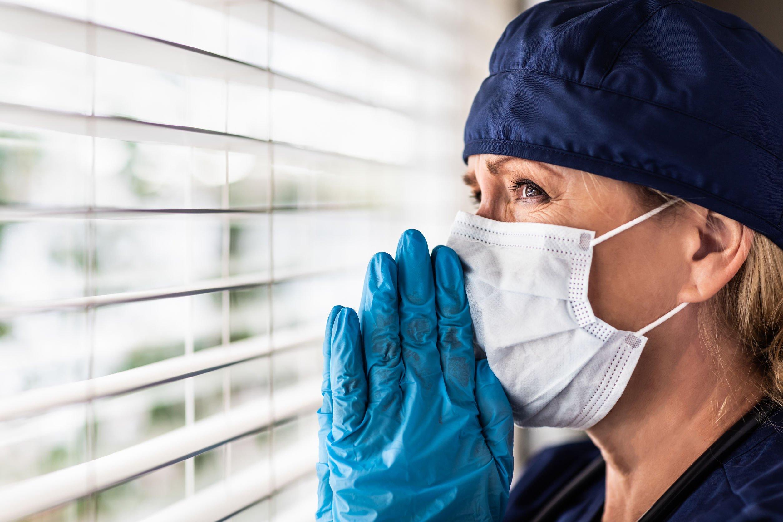 Enfermeira com os olhos cheios de lágrimas, olhando  para janela, com as mãos unidas em sinal de oração