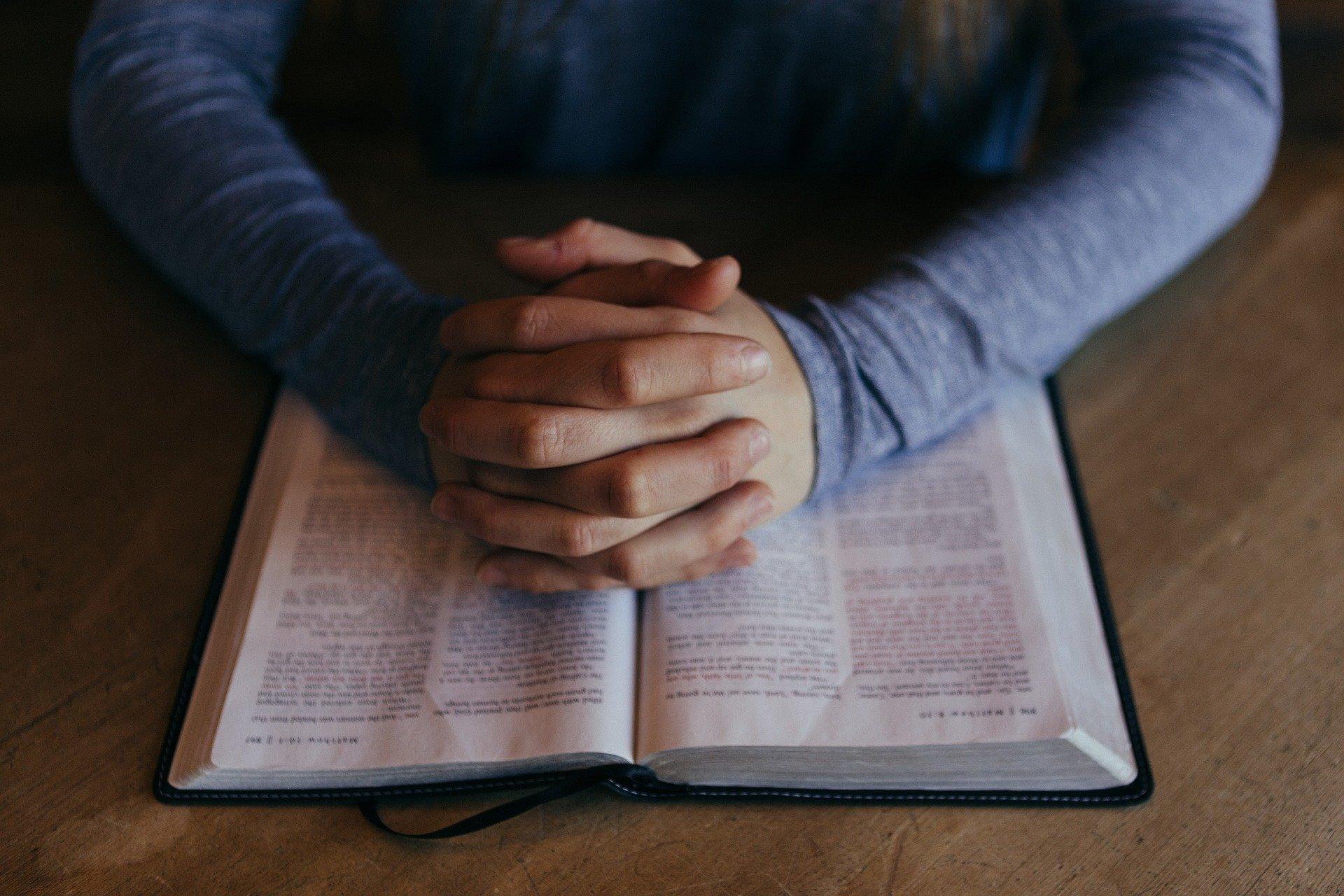 Pessoa com as mãos unidas sobre a bíblia aberta