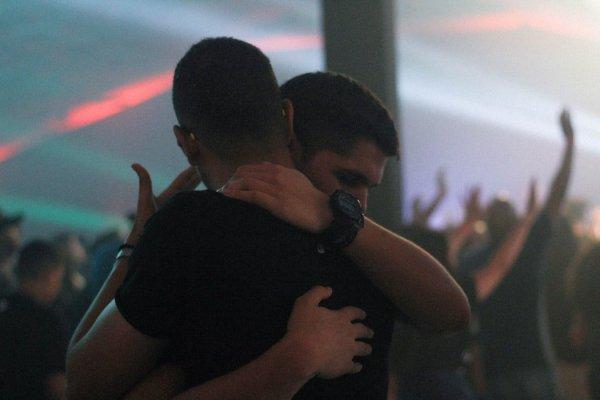 Homens amigos se abraçando em culto de igreja