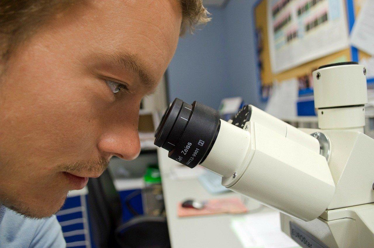 Homem olhando em microscópio de laboratório