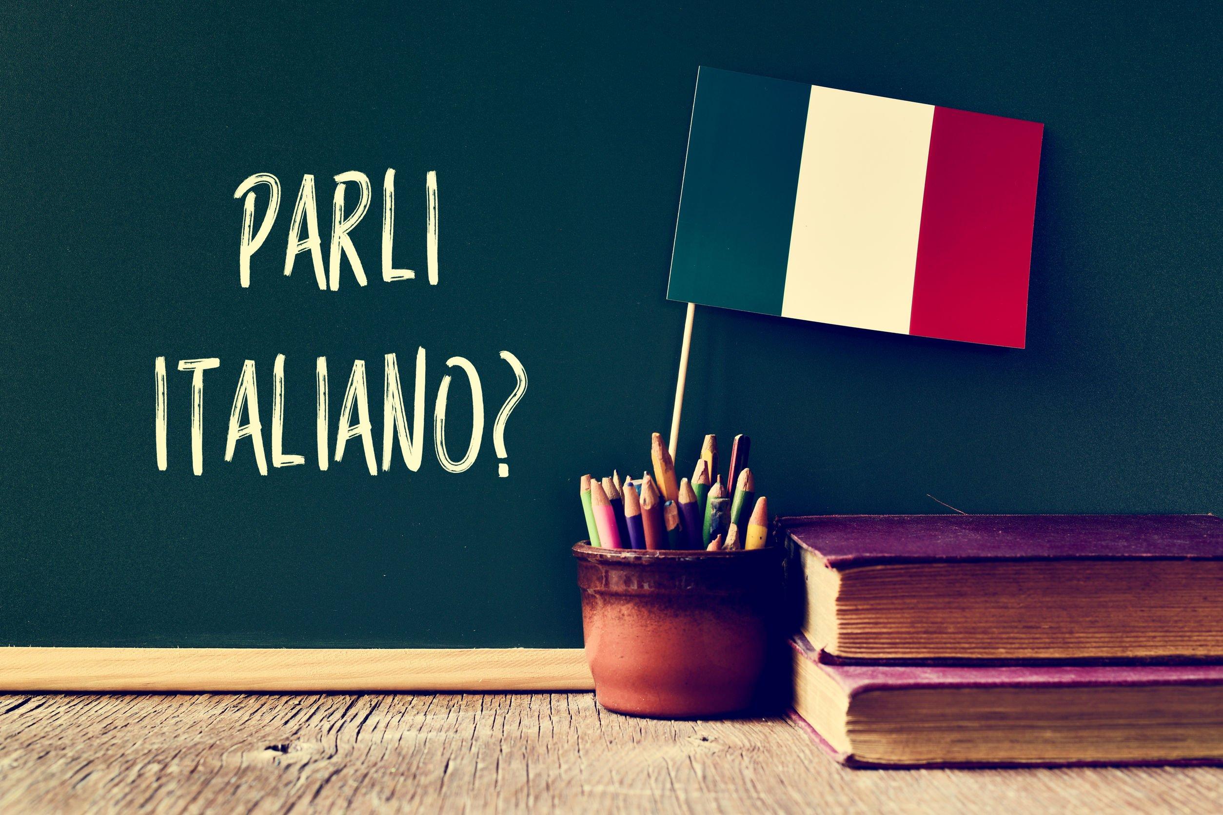 Lousa com a frase 'fala italiano' escrito em italiano atrás de porta lápis com miniatura de bandeira da itália