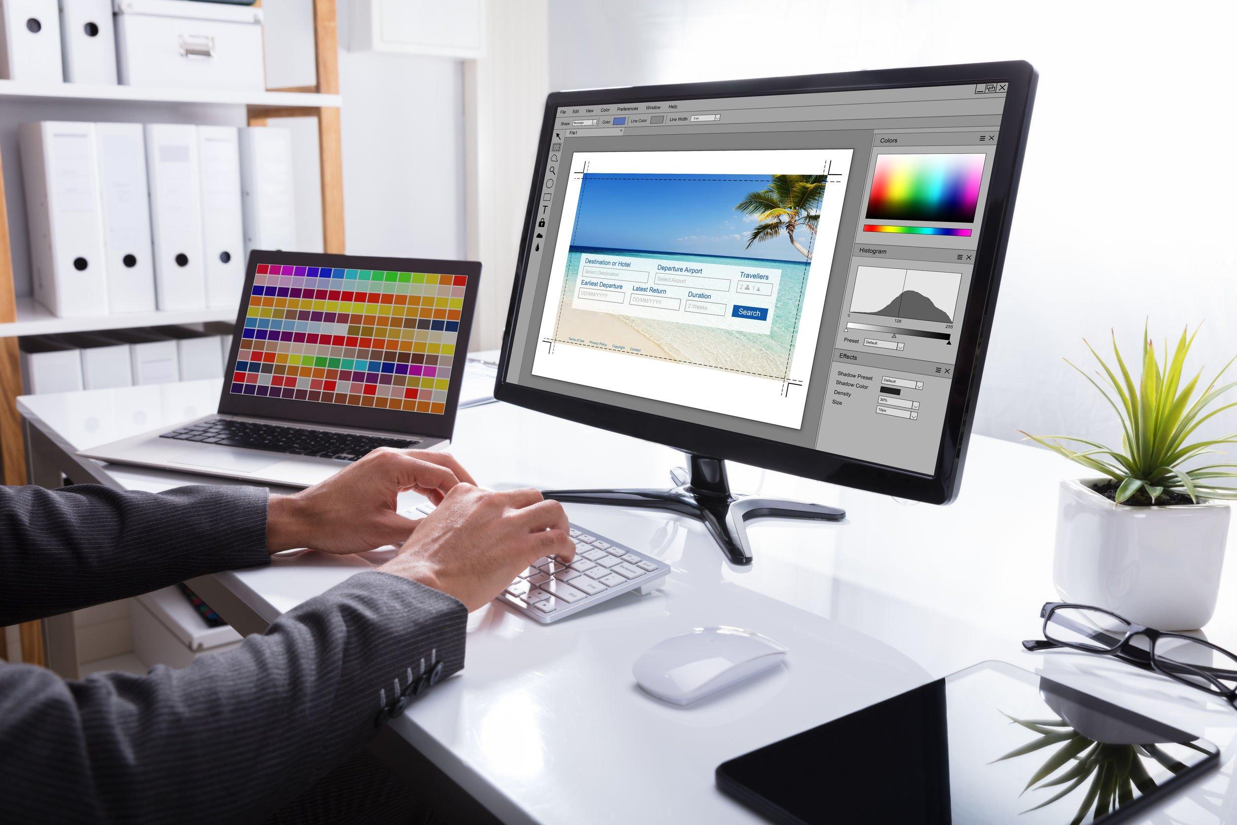Homem sentado mexendo em software de edição de imagem em computador