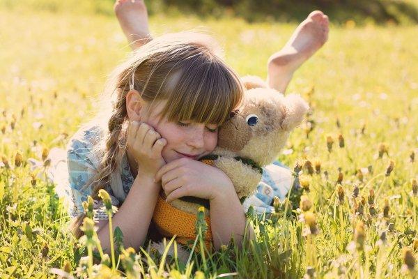 Menina segurando ursinho de pelúcia deitada em gramado