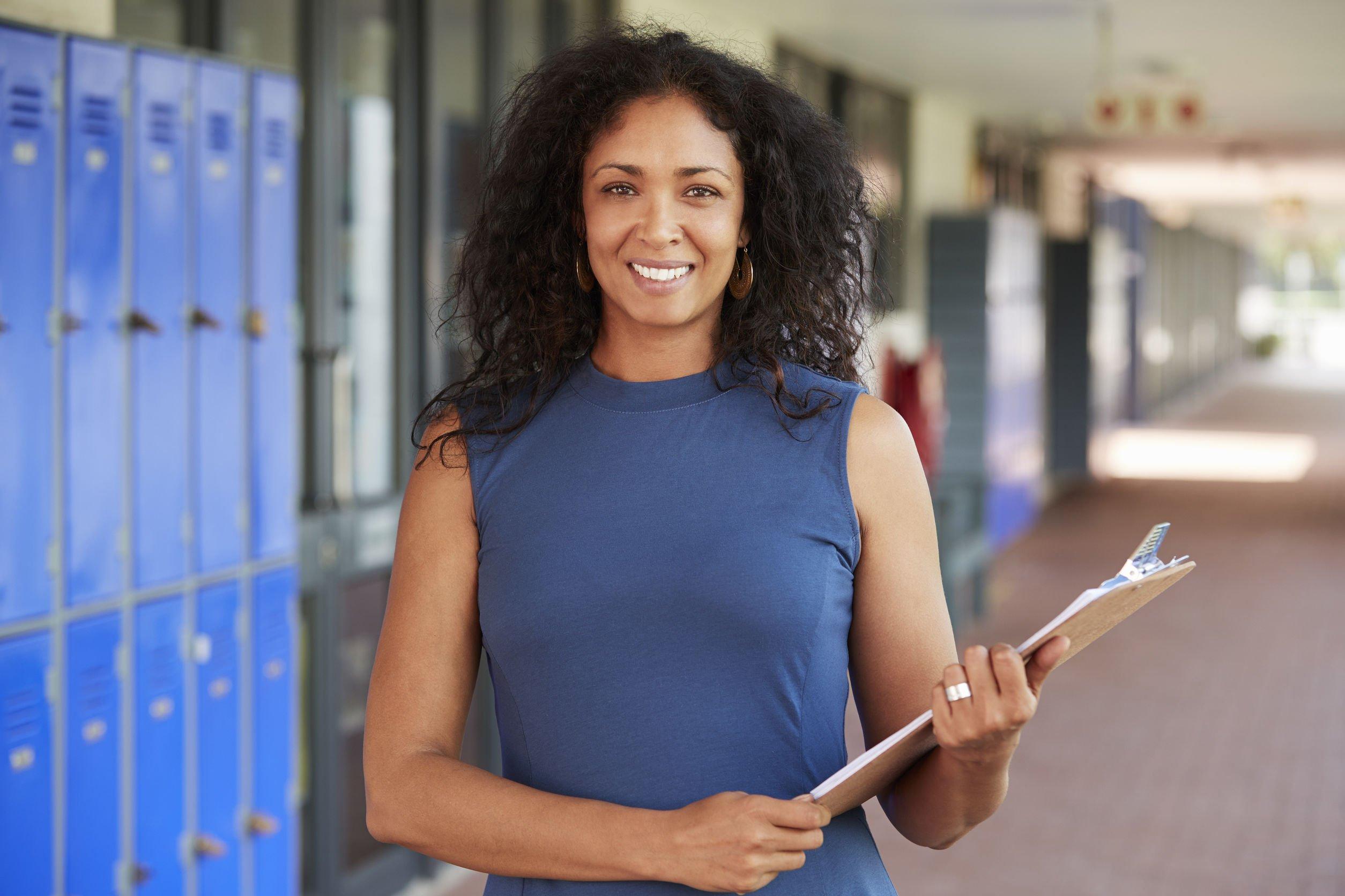 Professora negra segurando prancheta, sorrindo, em corredor de colégio