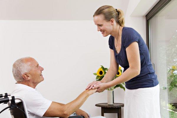 Mulher segurando a mão de idoso.