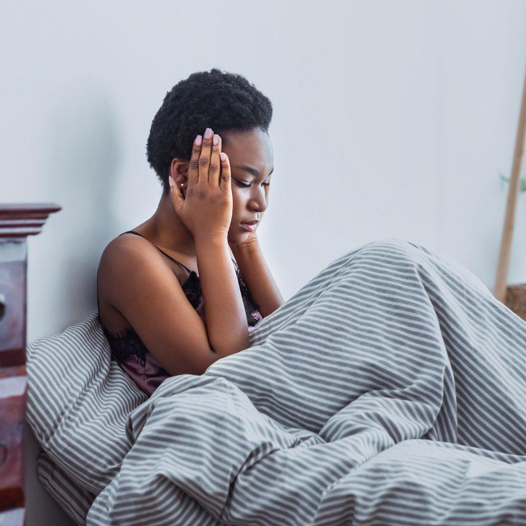 Imagem de uma mulher com as mãos na cabeça, deitada na cama