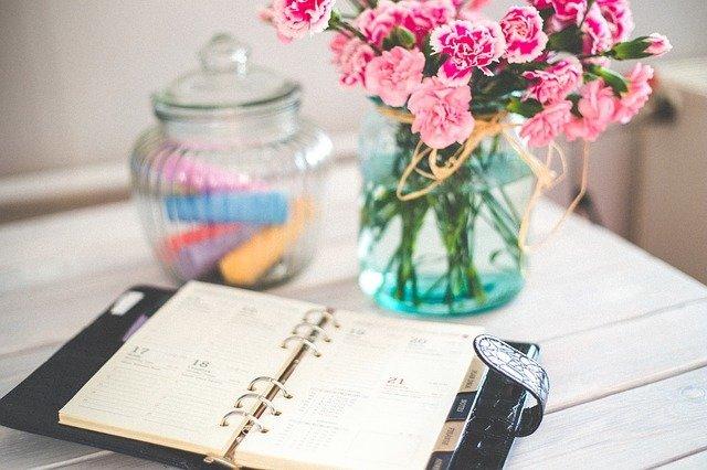 Mesa com agenda e vaso de flores em cima