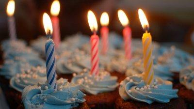 Bolo de aniversário com velas coloridas com letras formando a expressão feliz aniversário em inglês