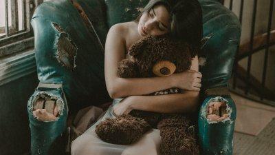 Mulher sentada em poltrona abraçando ursinho de pelúcia