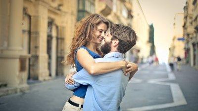 Homem beijando testa de mulher.