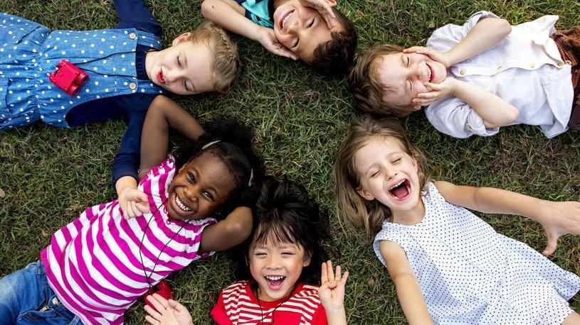 Crianças deitadas em círculo na grama vistas de cima sorrindo