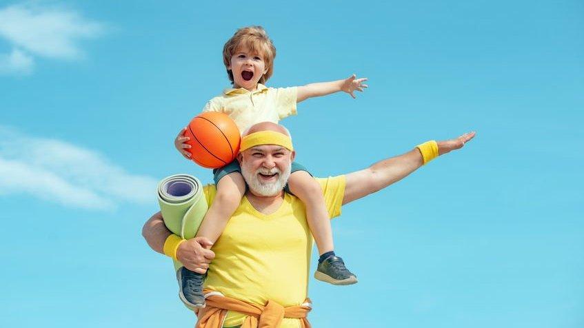 Avô carregando neto, com bola de basquete na mão