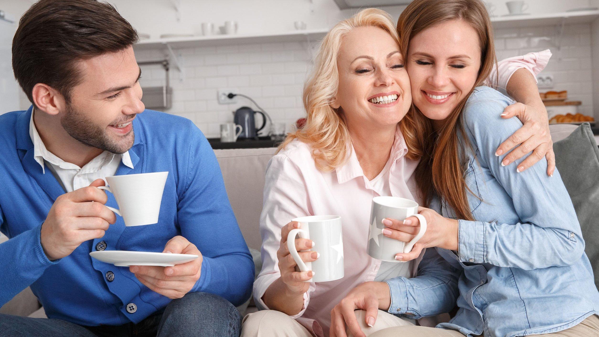 Mulher e sua sogra sentadas no sofá ao lado do marido, abraçadas e rindo.