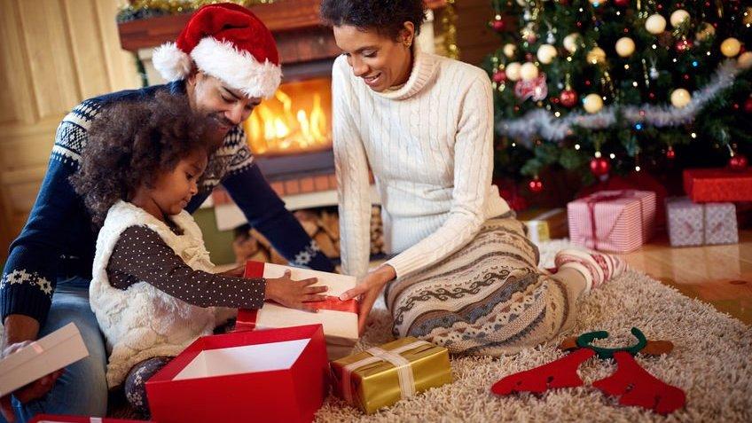 Pais sorrindo abrindo presentes de natal com a filha