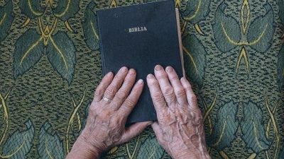 Idoso com mão sobre Bíblia