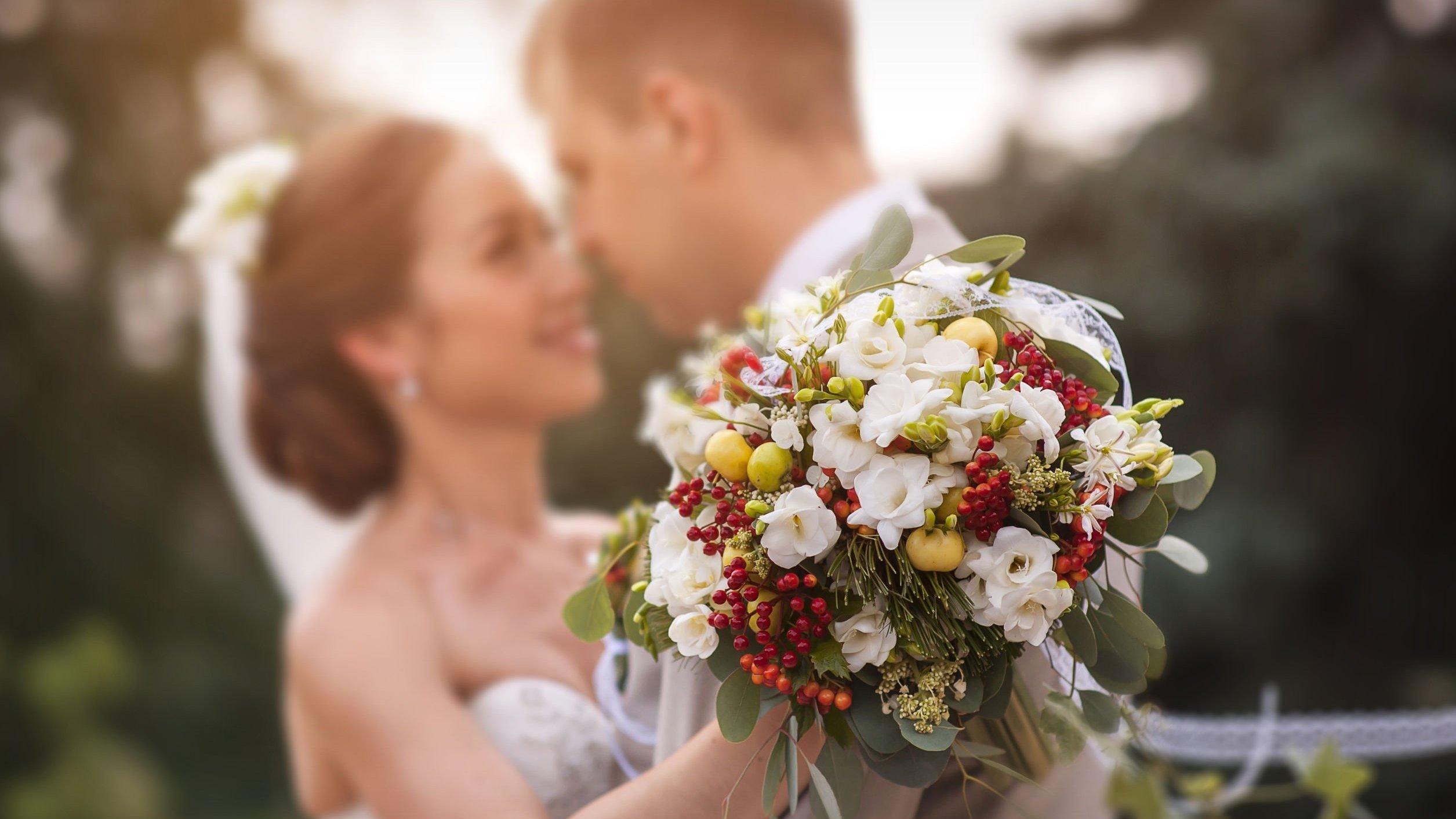 Noiva segurando um buquê de flores enquanto abraça o noivo