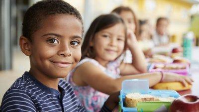 Crianças sentadas lado a lado em frente a uma mesa, com lancheiras e sanduíches. Em foco está um menino, e ao lado dele perdendo o foco com a distância, duas meninas.