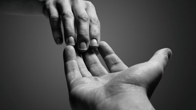Duas mãos estendidas de pessoas diferentes, se tocando apenas pelas pontas dos dedos.