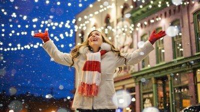 Menina no colo de mulher colocando estrela no topo de árvore de Natal