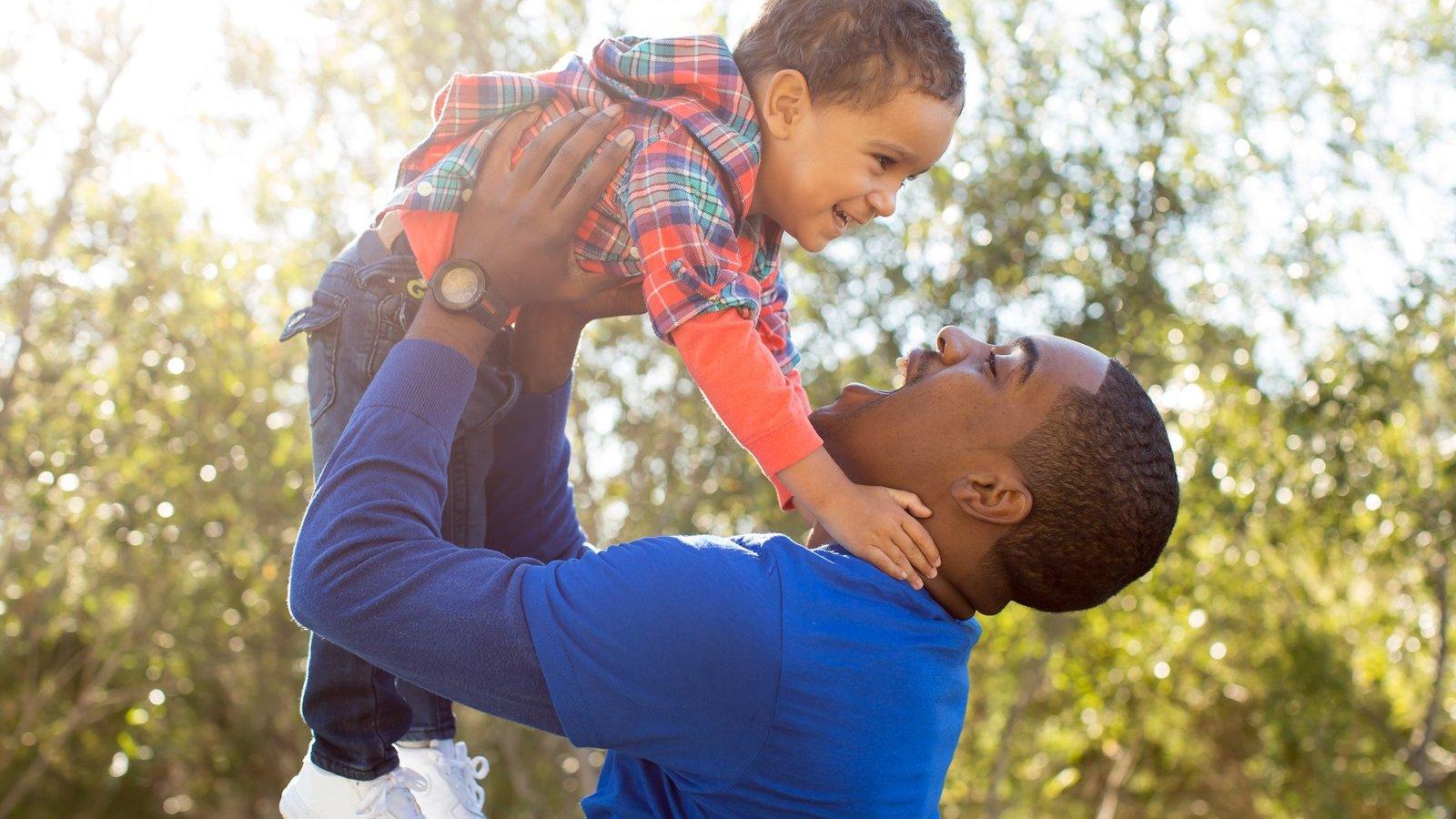Homem com a boca aberta segura um menino pequeno para o alto, que ri com a atitude.
