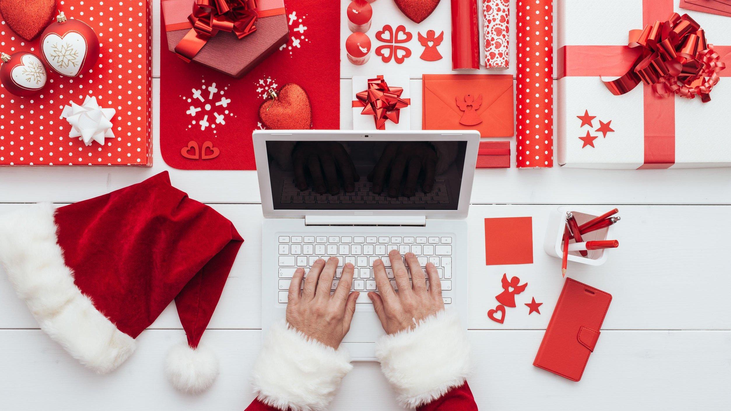 Mãos brancas manuseando um laptop branco com adereços natalinos ao redor.