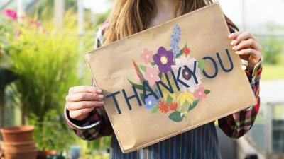 Menina segurando placa escrito Thank You